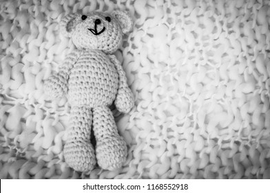 A soft teddy bear, toy for infant, isolated on a white blanket background. Sudden infant death syndrome stock image. Child death, abuse, harassment, rape, abort, abortion concept black and white image
