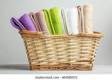 Soft terry towels in a basket on a wooden panel on gray background.