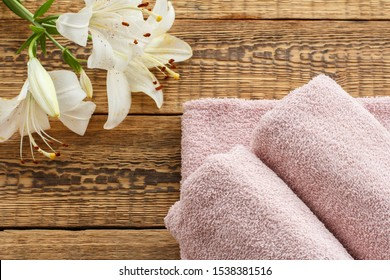 Soft terry towels with bouquet of white lily flowers on wooden boards. Top view.