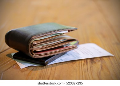 Soft tone of Money and credit card in a leather wallet on wooden table and bill slip background