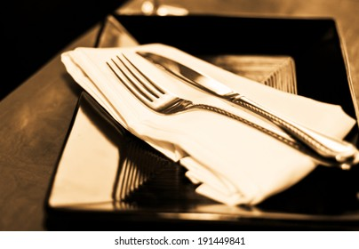 A soft toned image of a table setting with plate, napkin and utensils