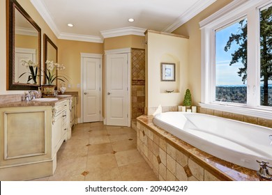 Soft tones bathroom interior with tile floor and tile wall trim, antique vanity with mirror and round bath tub in luxury house