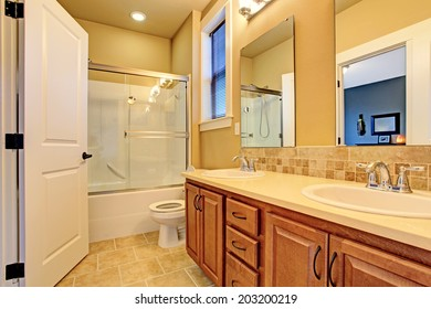 Soft tones bathroom interior. View of wooden bathroom vanity cabinet with two sinks and glass screened bath tub