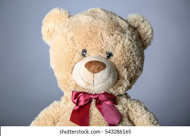 Soft toy brown teddy bear in a red bow tie with blak eyes