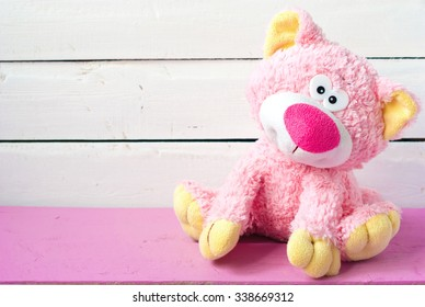 soft toy cute pink cat on a wooden background