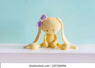 Soft toy knitted hare. Sitting yellow sad plush hare with a violet bow. Amigurumi.