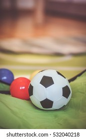 Soft toy soccer ball on green material in soft focus