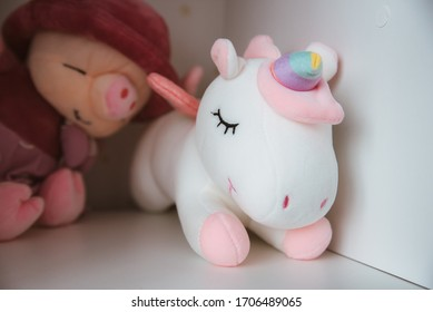 Soft toy white unicorn on the shelf close up horizontally
