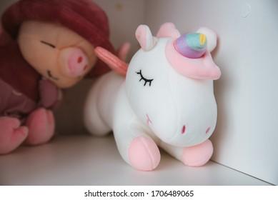 Soft toy white unicorn on the shelf close up horizontally