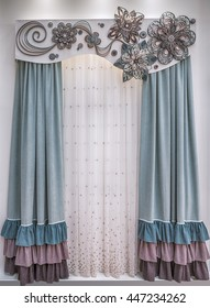 Soft velor curtains with colored frills, a light tulle and a stiff pelmet with lace applique.