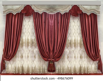 Soft velvet curtains of the saturated red color, the contrasting pelmet with the fringed and the tulle with the embroidery