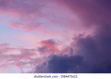 Soft vibrant colors in sunset sky with dramatic cumulus clouds as if on fire with blue sky and lit up magenta and red tones