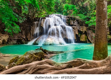 Soft waterfall, beautiful green water in a green tree forest on a tropical mountain at Erawan National Park, Thailand.