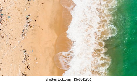 Soft wave of blue ocean on sandy beach with Plastic garbage and medical waste materials in andaman sea tropical beach with emerald clear sea - Aerial top view photo taken by drone