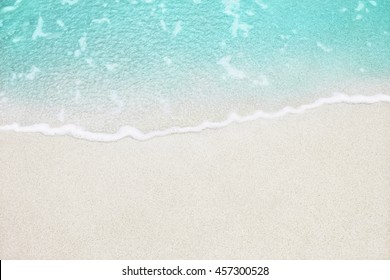Soft wave of blue ocean on sandy beach. Background.
