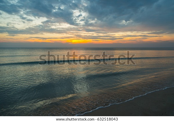 Soft wave of blue ocean on sandy beach during sunrise hour background