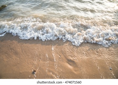 Soft wave of the sea on the sand beach with sunlight. Tropical sandy beach background with copy space. Top down view.