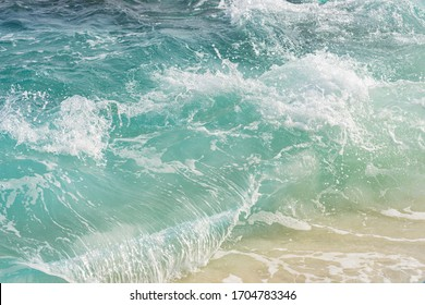 Soft waves of blue ocean on sandy beach. Background and copy space. Holiday concept.