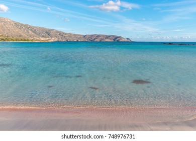 Soft waves of the sea on the pink sand and beautiful beach with cliffs.Coast of Crete island in Greece. Pink sand beach of famous Elafonisi