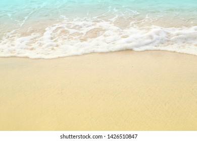 Soft white blue sea wave on clean brown sandy beach coast have copyspace