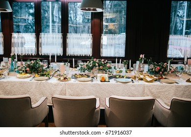 Soft white chairs stand at dinner table decorated with bouquets and candles