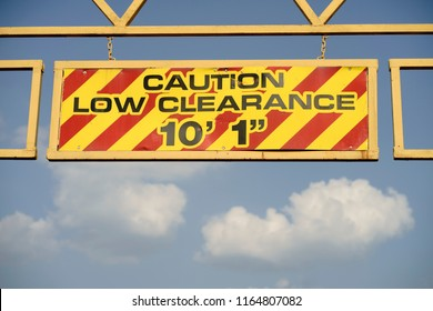 Soft white clouds against blue skies provide a nice background for a yellow low clearance sign
