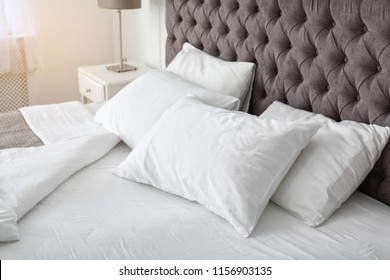 Soft white pillows on comfortable bed indoors