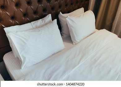 Soft white pillows on comfortable bed, closeup