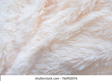 a soft white, plush micro fleece fabric blanket is swirled into a circular pattern background