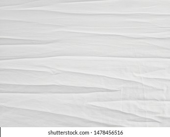 Soft white wrinkled fabric background for graphic design or wallpaper.
