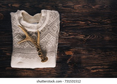 Soft wool sweater with deer antlers. Rustic and homey feel.