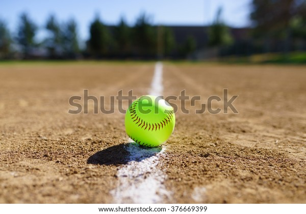 Softball in a softball field in California mountains on a white line
