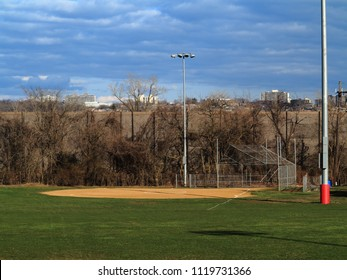 Softball Field - Sports venue with light towers and scenic blue sky and clouds.ball Filed