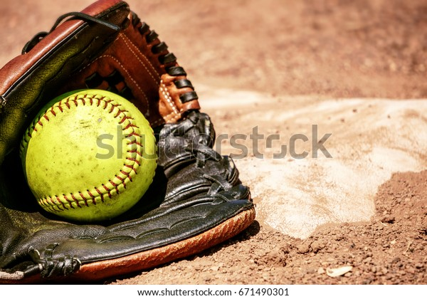 Softball and glove in front of the base.