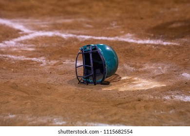 Softball helmet laying sideways on homeplate at the end of a game.