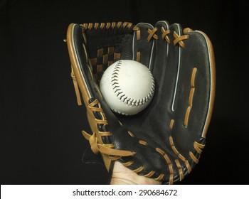 Softball mitt with white softball in webbing.