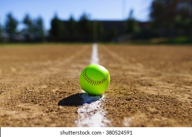 Softball on a white foul line at a softball field in California mountains