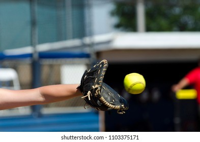 Softball Player About To Catch Yellow Ball In Mitt