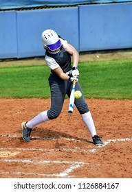 Softball Player at the Plate Swinging the Bat