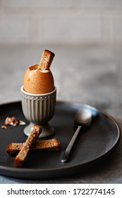 Soft-boiled egg in a eggcup with rye croutons for breakfast on a gray background. Free space for text. Selective focus.Vertical photo.