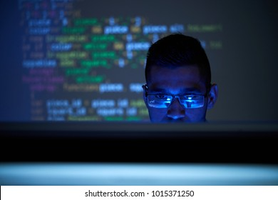 Software developer checking code on computer screen