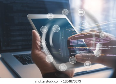 Software developer coding computer program with augmented reality dashboard, mobile app design with internet  icons on VR screen. Man hand using digital tablet, IoT Internet of Things concept
