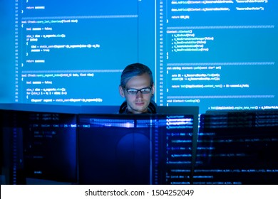 Software developer freelancer man male work with program code C++, Java, Javascript on wide displays at night. Develops new web desktop mobile application or framework. Projector futuristic background