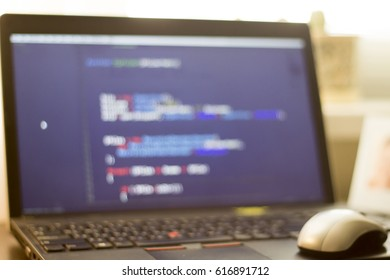 Software developer laptop on the desk. Blurry photo of developer workspace. Abstract information technology modern background.  Unfocused laptop display with code.