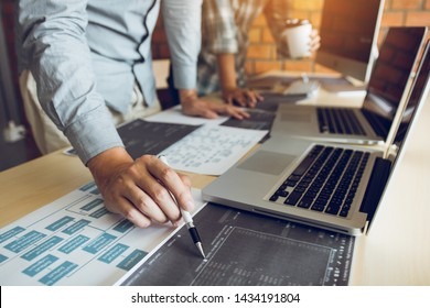 Software developer is pointing to the paper working and analyzing together the code written into the program on the computer.