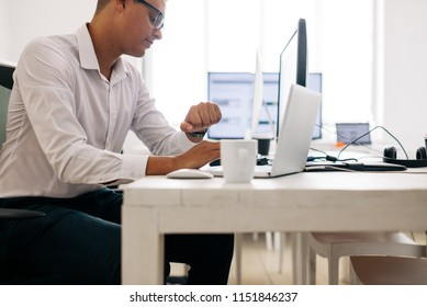 Software developer sitting at his office desk working on laptop and desktop computer simultaneously. Man wearing spectacles looking at his wrist watch while working on laptop computer in office.