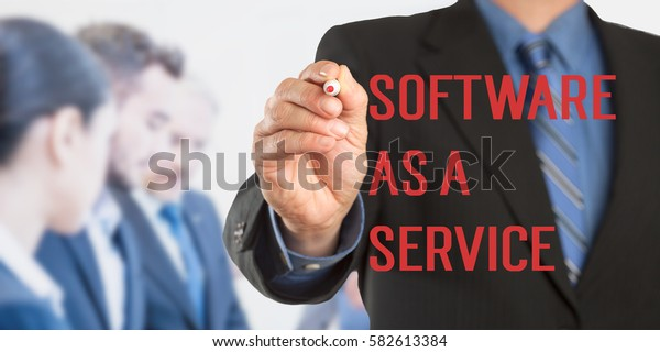 Software As A Service, Male hand in business wear holding a thick pen writing, with office team blurred in background, digital composing.