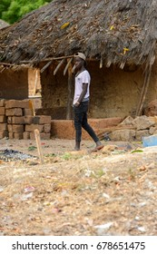 SOGA, GUINEA BISSAU - MAY 5, 2017: Unidentified local boy in a cap walks near the shack in a village of the Soga island. People in G.-Bissau still suffer of poverty