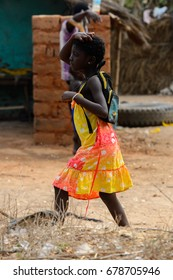 SOGA, GUINEA BISSAU - MAY 5, 2017: Unidentified local little girl in colored dress with backpack walks in a village of the Soga island. People in G.-Bissau still suffer of poverty