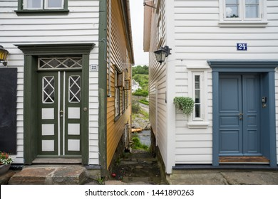 Sogndalstrand / Norway - June 20 2019: Sogndalstrand, harbor village located at the mouth of the river Sokno. Street view, gap between two houses and wooden boat that is behind the buildings.
